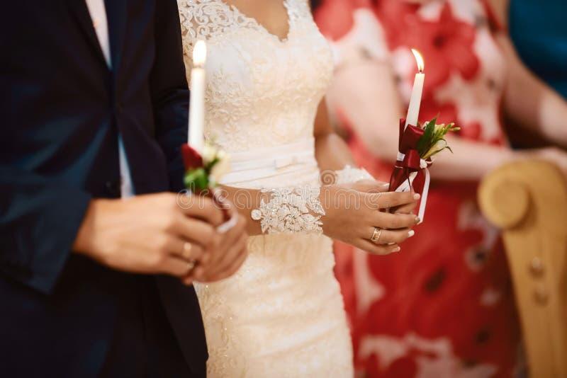 Novia feliz y novio elegante que llevan a cabo la ceremonia de boda de las velas, par de la boda en el matrimonio en iglesia, mom fotos de archivo