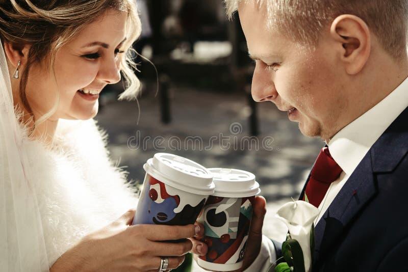 Novia feliz y novio elegante que sostienen las tazas de co urbano delicioso imagen de archivo libre de regalías