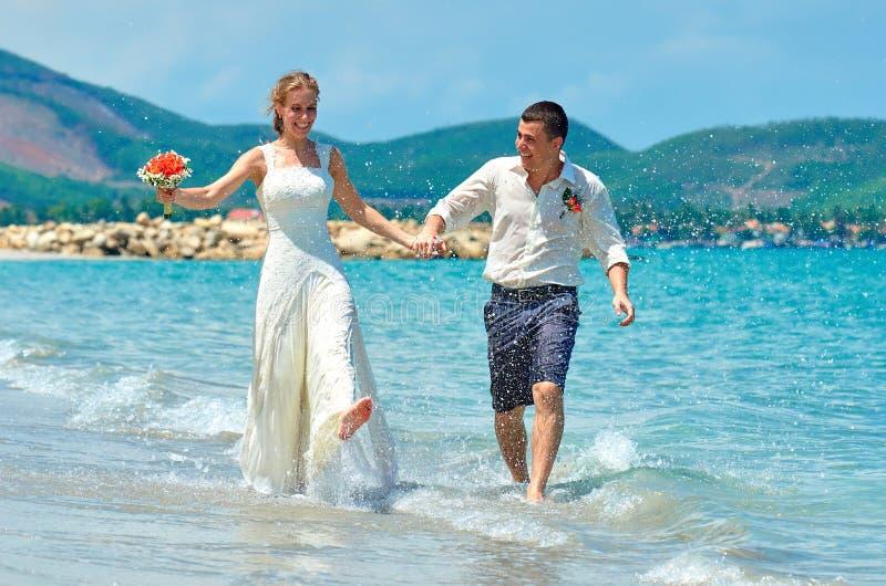 Novia feliz y novio que corren en una playa tropical hermosa imagen de archivo