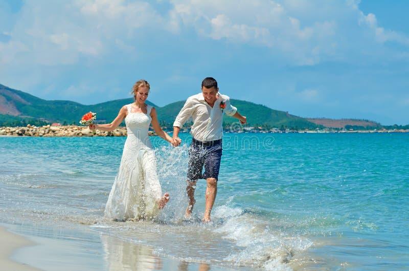 Novia feliz y novio que corren en una playa tropical hermosa imágenes de archivo libres de regalías