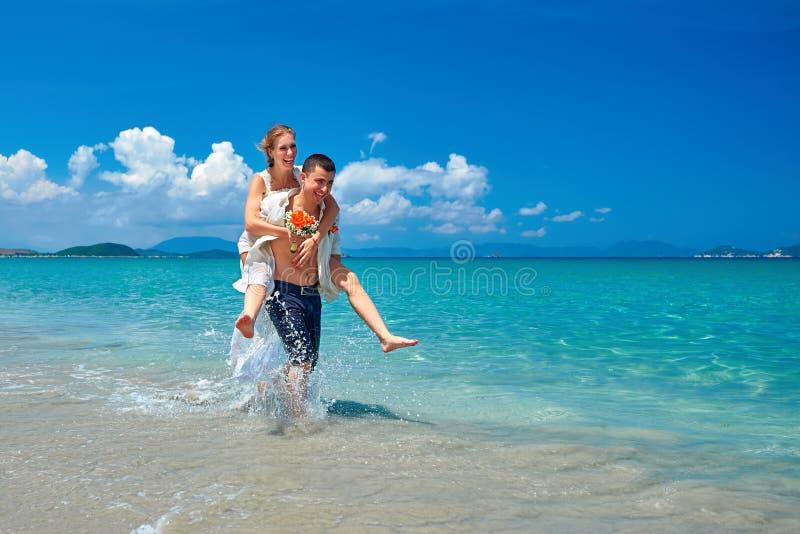 Novia feliz y novio que corren en una playa tropical hermosa imagenes de archivo