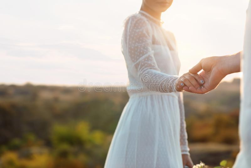 Novia feliz y novio que llevan a cabo las manos al aire libre foto de archivo libre de regalías