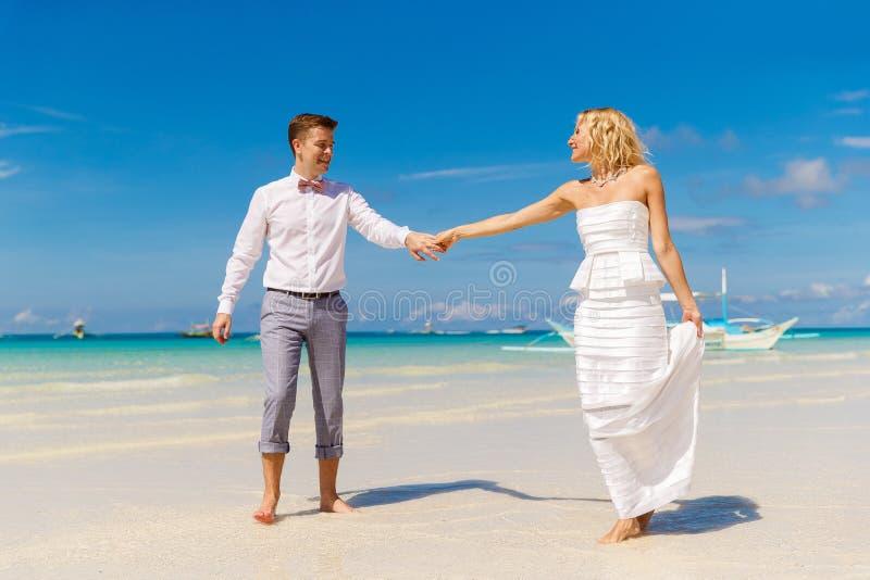 Novia feliz y novio que se divierten en la playa tropical tropical foto de archivo libre de regalías