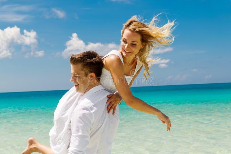 Novia feliz y novio que se divierten en la playa tropical tropical foto de archivo