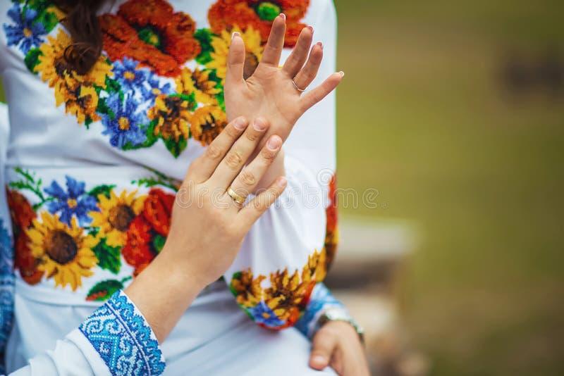 Novia feliz y novio ucranianos que muestran sus manos con los anillos después de la ceremonia, ropa bordada fotografía de archivo libre de regalías
