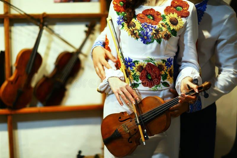Novia feliz y novio ucranianos que muestran sus manos con los anillos después de la ceremonia, ropa bordada, violín viejo fotografía de archivo