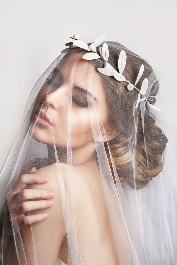Novia hermosa con el peinado de la boda de la moda - en el fondo blanco Retrato del primer de la novia magnífica joven fotografía de archivo