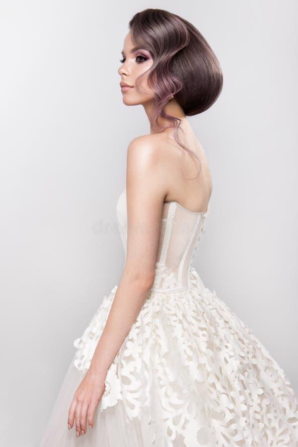 Novia hermosa con el peinado de la boda de la moda - en el fondo blanco fotografía de archivo