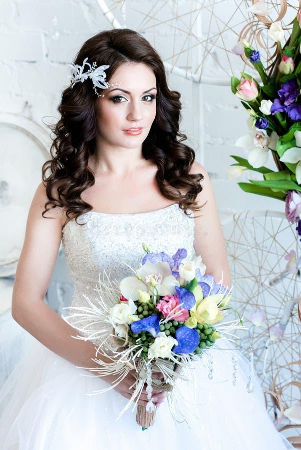 Novia hermosa con las flores que nos miran feliz imagenes de archivo