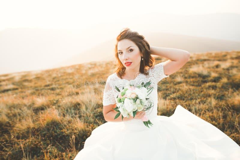 Novia hermosa con un ramo en fondo de la montaña en la puesta del sol fotos de archivo libres de regalías