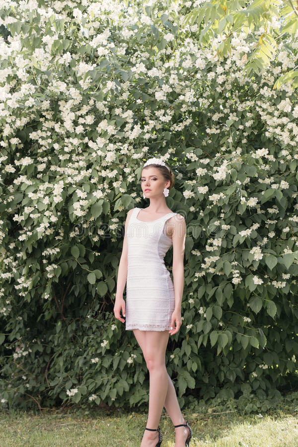 Novia hermosa de la muchacha en un vestido blanco corto con una corona de flores en el jardín que camina entre los árboles del ja fotos de archivo libres de regalías