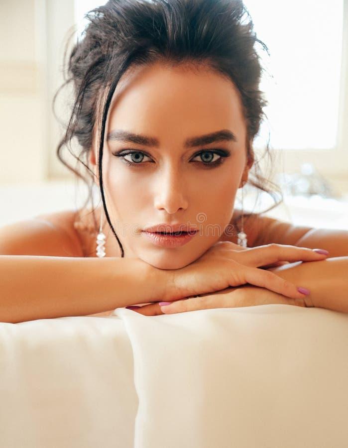 Novia hermosa de la mujer con el pelo oscuro en el vestido que se casa lujoso que presenta en baño fotografía de archivo libre de regalías