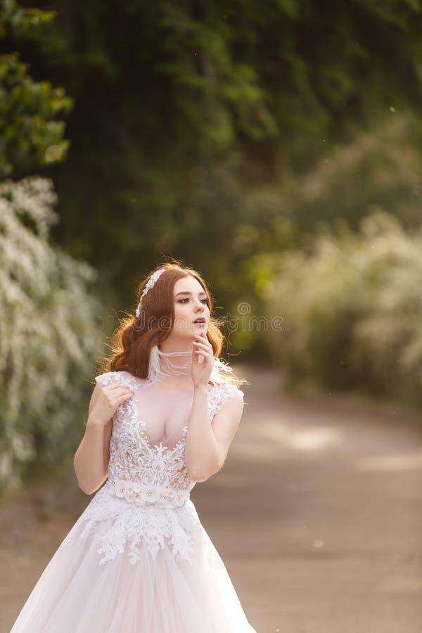 Novia hermosa del pelirrojo en vestido de boda fantástico en jardín floreciente imagenes de archivo