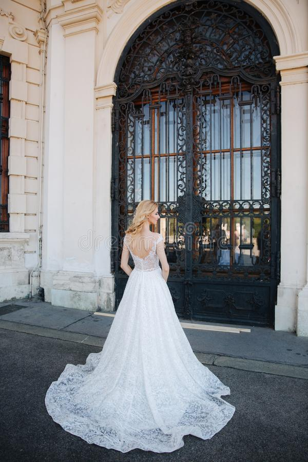 Novia hermosa del pelo rubio cerca del pacale Mujeres en un vestido que se casa blanco elegante imagen de archivo