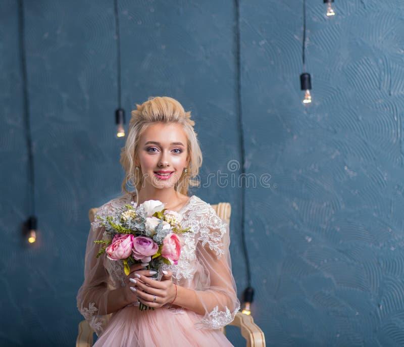 Novia hermosa en el vestido de boda que presenta con el ramo en manos fotografía de archivo