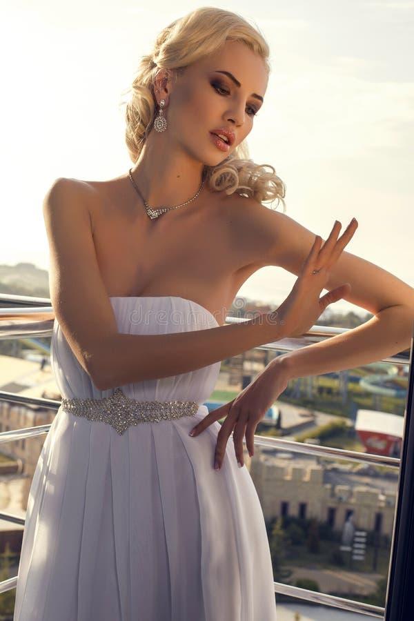 Novia hermosa en el vestido elegante que presenta en el balcón imágenes de archivo libres de regalías