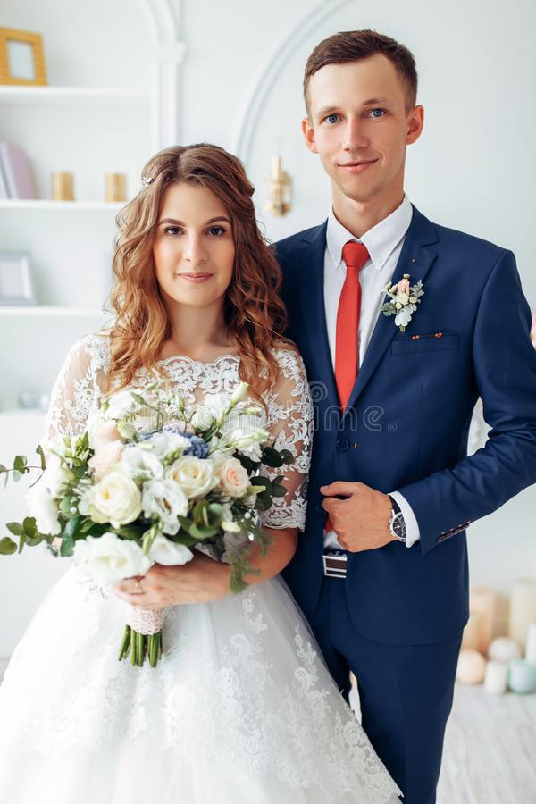 Novia hermosa en el vestido y el novio blancos en el traje, presentando en el interior blanco del estudio, boda imagenes de archivo