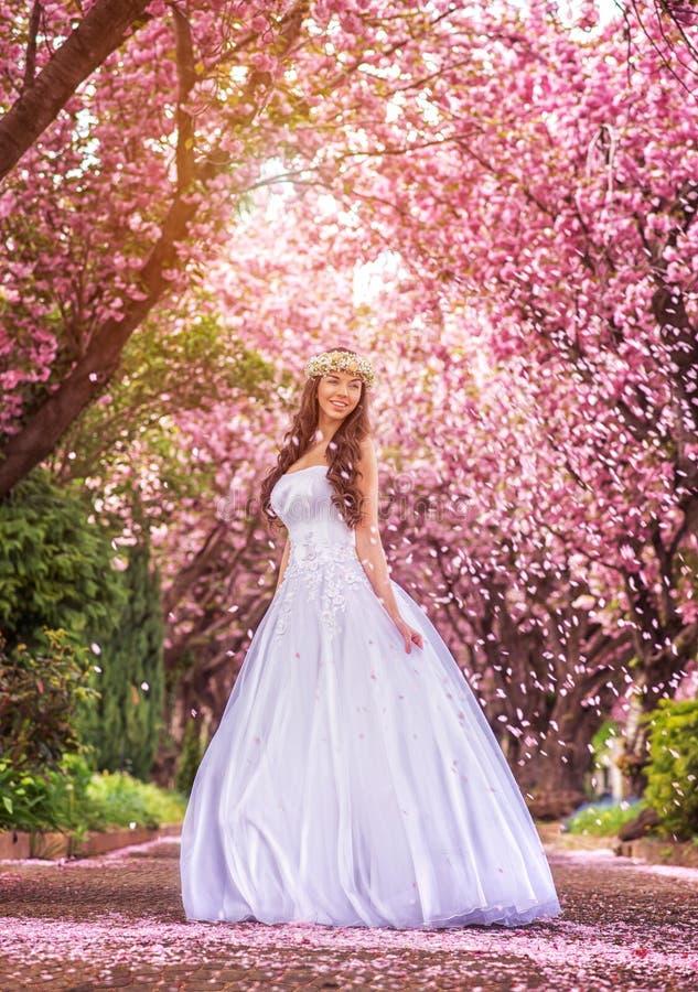Novia hermosa en un vestido blanco debajo de los pétalos del árbol y de la flor de Sakura foto de archivo