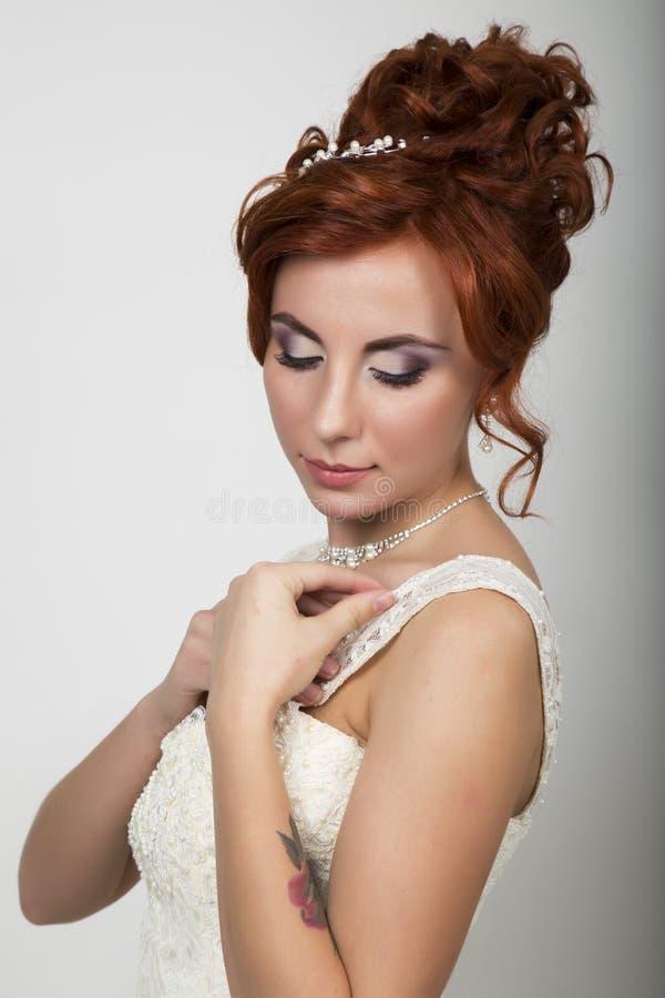 Novia hermosa en un vestido de boda con un maquillaje y un peinado de la boda fotos de archivo