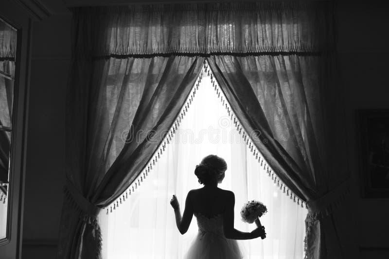 Novia hermosa en un vestido de boda, por la ventana imágenes de archivo libres de regalías