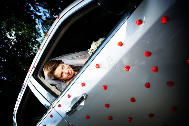 Novia hermosa en una limusina de la boda imagen de archivo libre de regalías