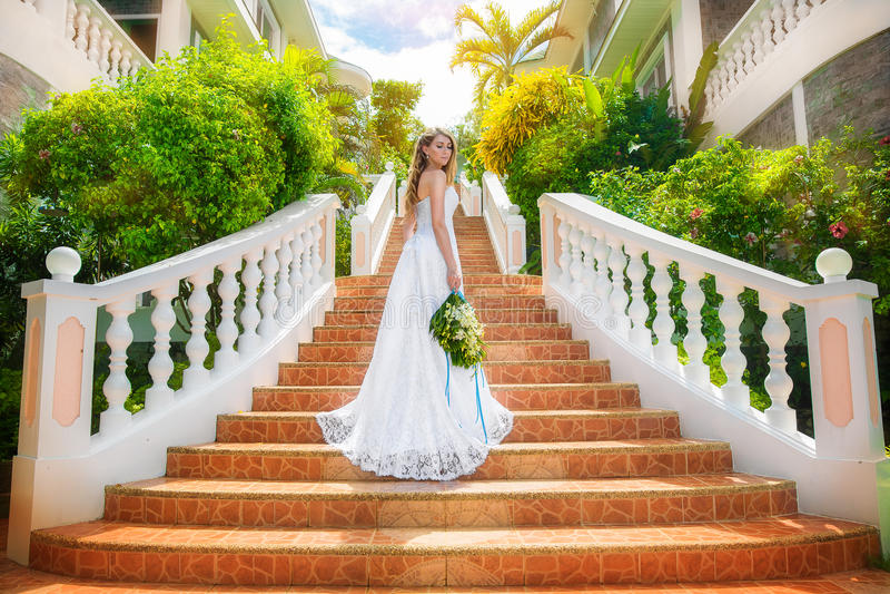 Novia hermosa en vestido de boda con el tren largo que se coloca en imagenes de archivo
