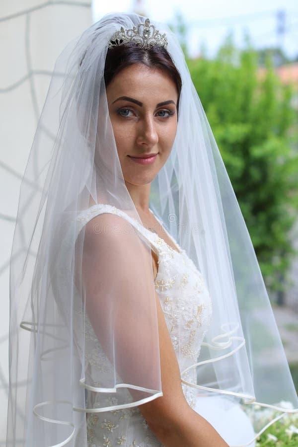 Novia hermosa en vestido de boda de la moda en fondo natural La novia joven imponente es incre?blemente feliz boda imagenes de archivo