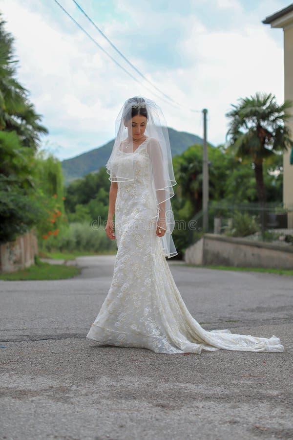 Novia hermosa en vestido de boda de la moda en fondo natural La novia joven imponente es incre?blemente feliz boda fotografía de archivo