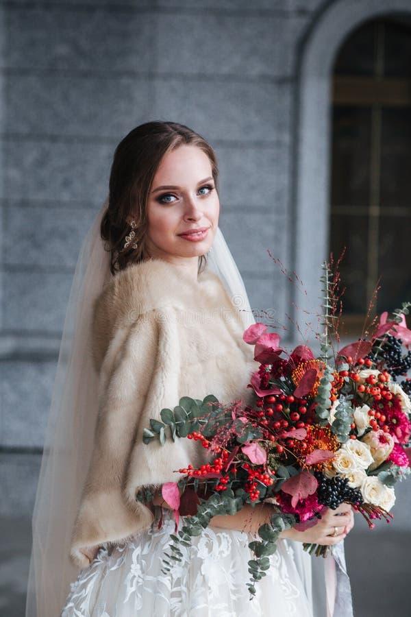 Novia hermosa en vestido de boda de la moda y abrigo de pieles en d?a de boda Ramo nupcial imagen de archivo libre de regalías