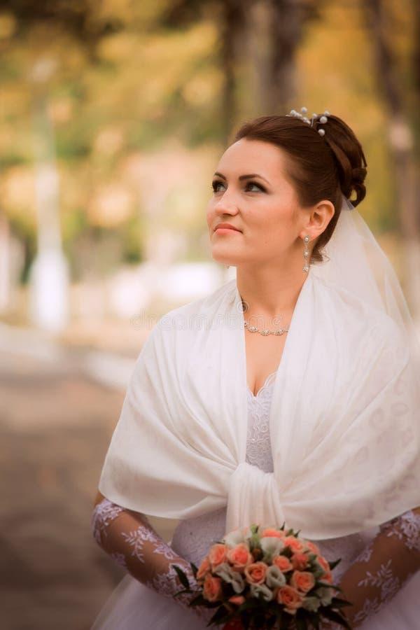 Novia hermosa en vestido de boda y ramo nupcial, mujer feliz del recién casado con las flores de la boda, mujer con maquillaje de imágenes de archivo libres de regalías