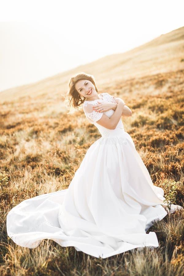 Novia hermosa feliz afuera en un prado del verano en la puesta del sol con la visión perfecta imagenes de archivo