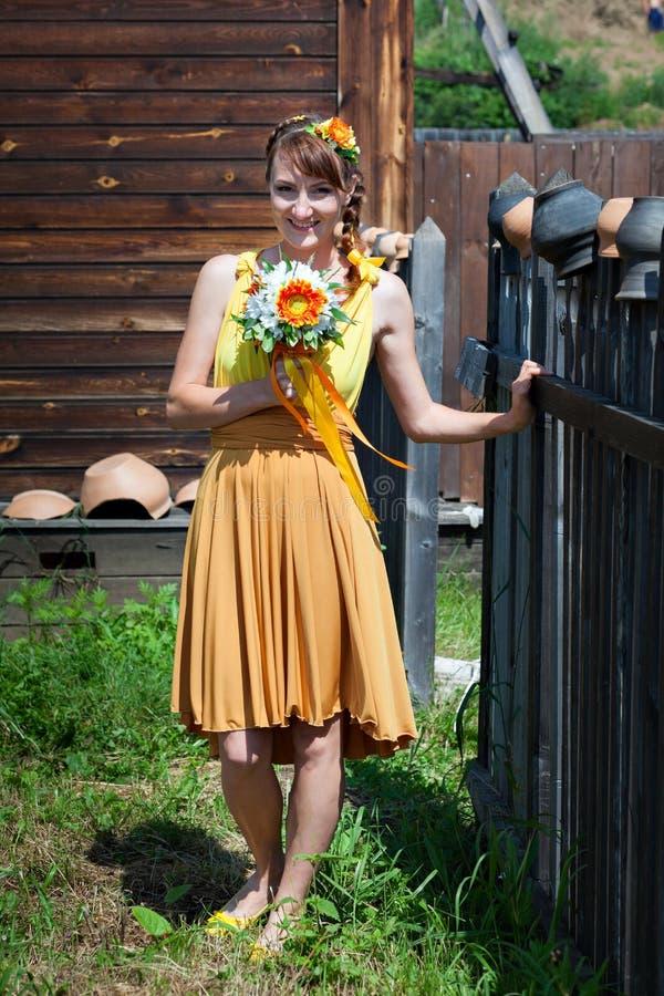 Novia hermosa joven de la muchacha en un vestido anaranjado brillante en la casa de madera rusa Flores de la decoración en su pel fotos de archivo