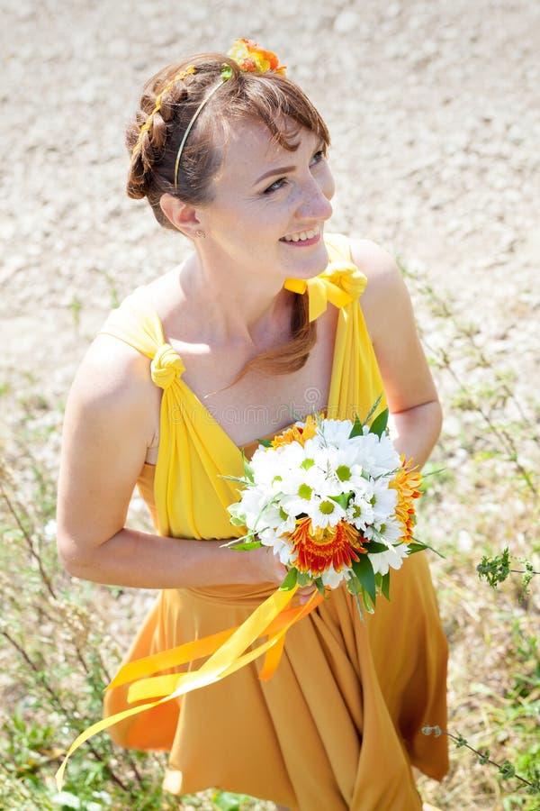 Novia hermosa joven de la muchacha en un vestido anaranjado brillante Ramo del verano en manos del fotografía de archivo libre de regalías