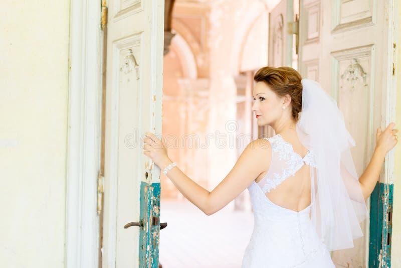 Novia hermosa joven en el vestido blanco cerca de la puerta vieja fotos de archivo
