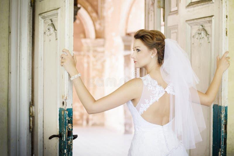 Novia hermosa joven en el vestido blanco cerca de la puerta vieja imagenes de archivo
