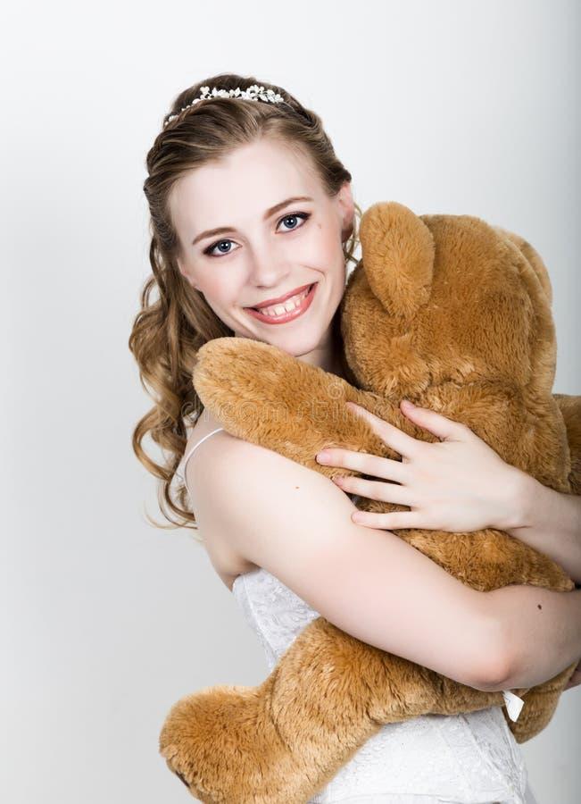 Novia hermosa joven que sostiene un oso de peluche, abrazan suavemente fotografía de archivo