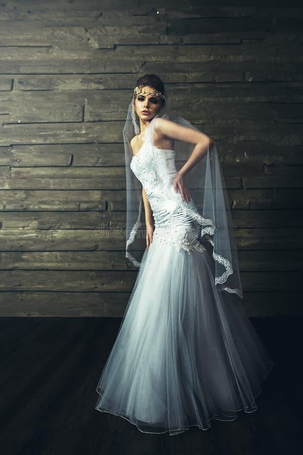 Novia hermosa joven sensualy que presenta en el vestido de boda blanco imagen de archivo
