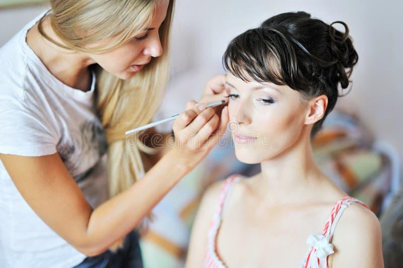 Novia hermosa que aplica maquillaje de la boda del artista de maquillaje fotos de archivo libres de regalías
