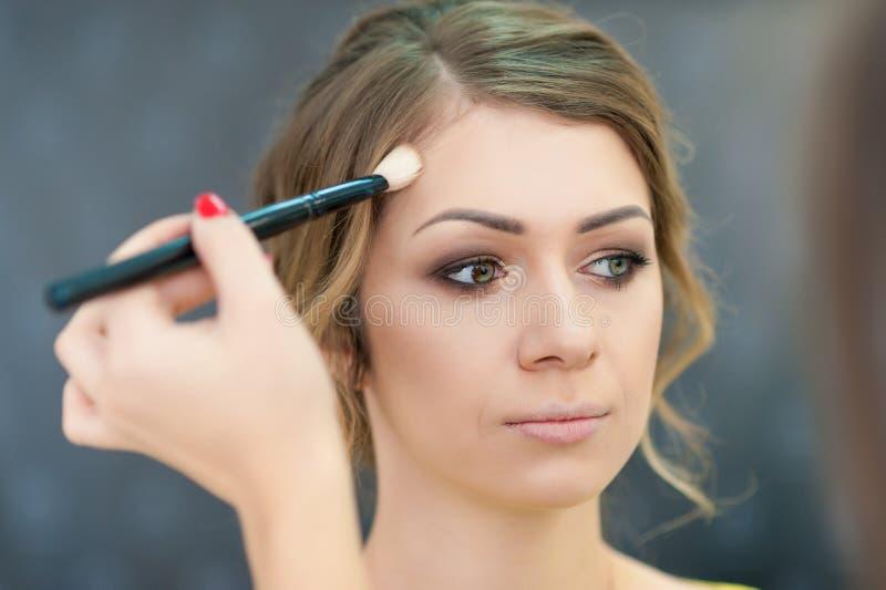 Novia hermosa que se aplica casandose maquillaje en salón imagen de archivo