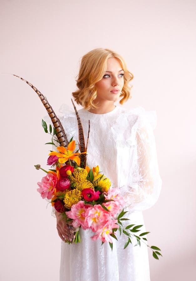 Novia hermosa que sostiene el ramo de la boda en manos foto de archivo