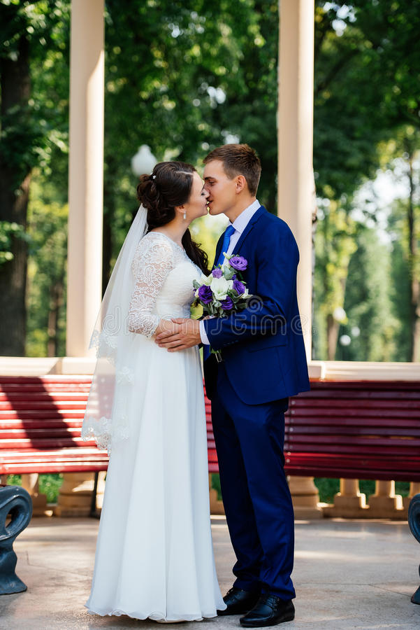 Novia hermosa y novio jovenes que se besan cerca de un banco de madera en el parque Pares de la boda en amor en el día del wedd imagenes de archivo