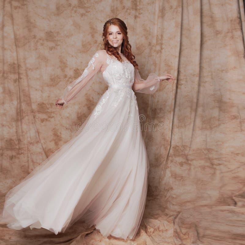 Novia hermosa y romántica en vestido de boda con las mangas largas Mujer redheaded joven en vestido de boda fotos de archivo libres de regalías