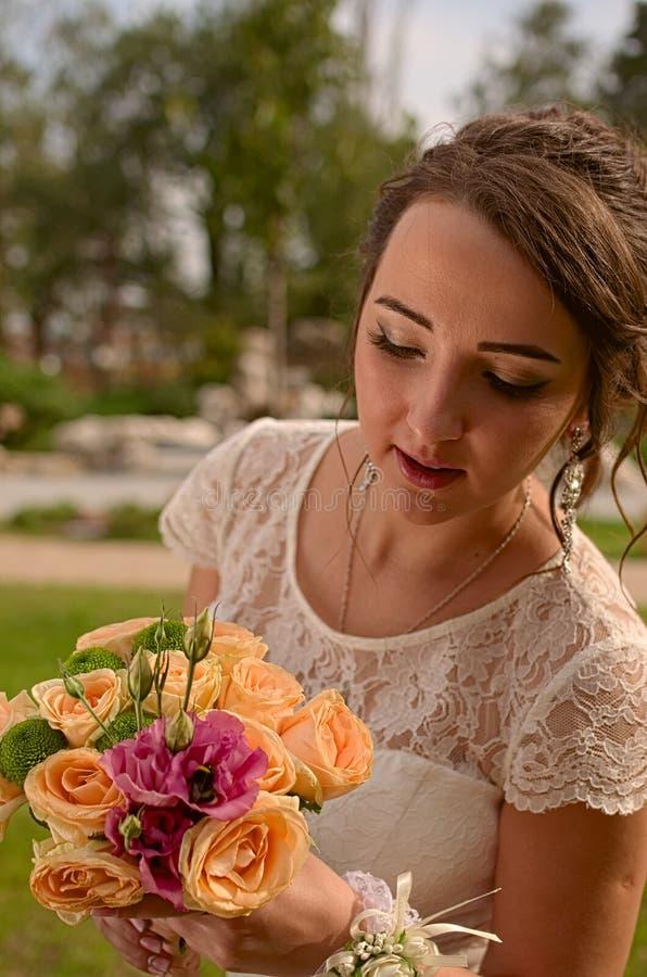 Novia increíblemente hermosa con el ramo de rosas Abejorro grande en el ramo de la novia Muchacha de pelo largo en vestido de bod foto de archivo