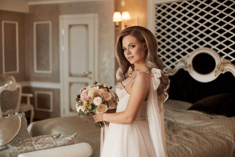 Novia joven elegante en el vestido de marfil que guarda el ramo hermoso imágenes de archivo libres de regalías