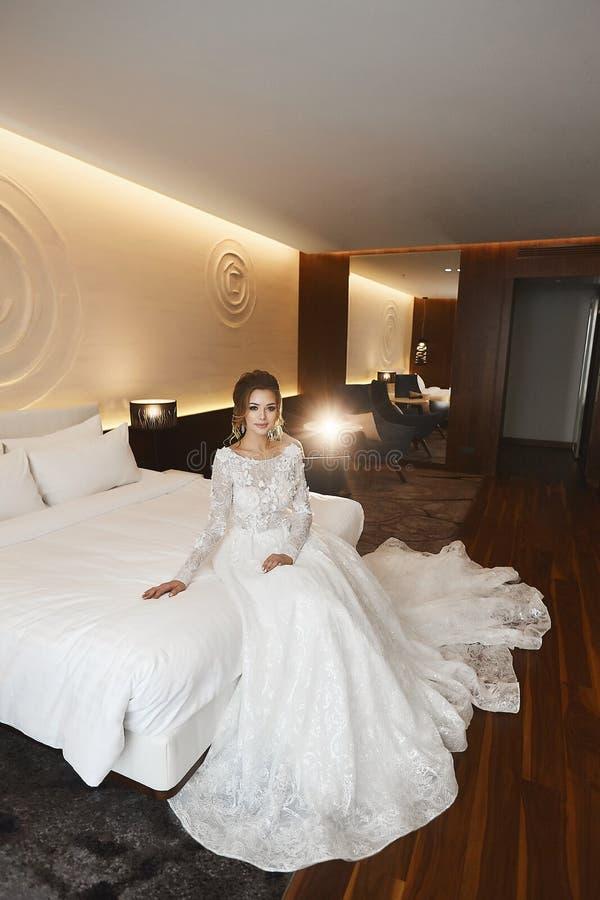 Novia joven elegante y hermosa en el vestido del cordón que presenta en la cama en el interior del lujo fotos de archivo libres de regalías