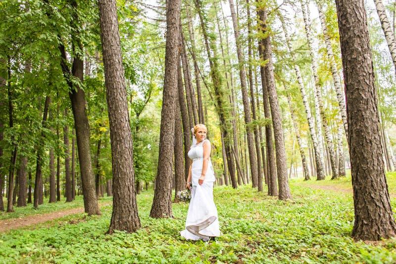 Novia joven en el vestido de boda que sostiene el ramo, al aire libre fotografía de archivo