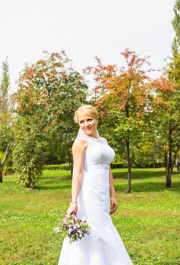 Novia joven en el vestido de boda que sostiene el ramo, al aire libre fotografía de archivo libre de regalías