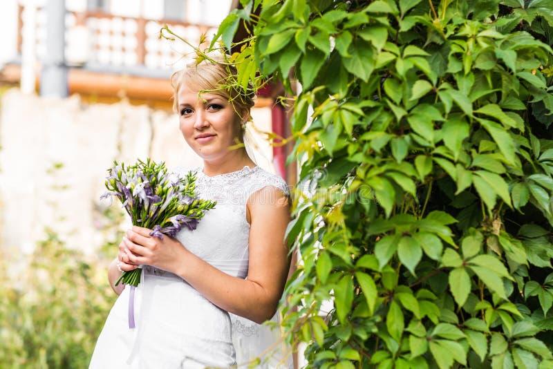 Novia joven en el vestido de boda que sostiene el ramo, al aire libre imagen de archivo