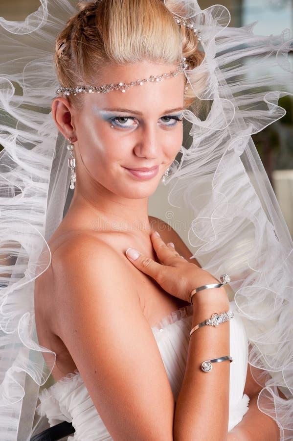 Novia joven en la alineada blanca con la tiara y el velo imagenes de archivo