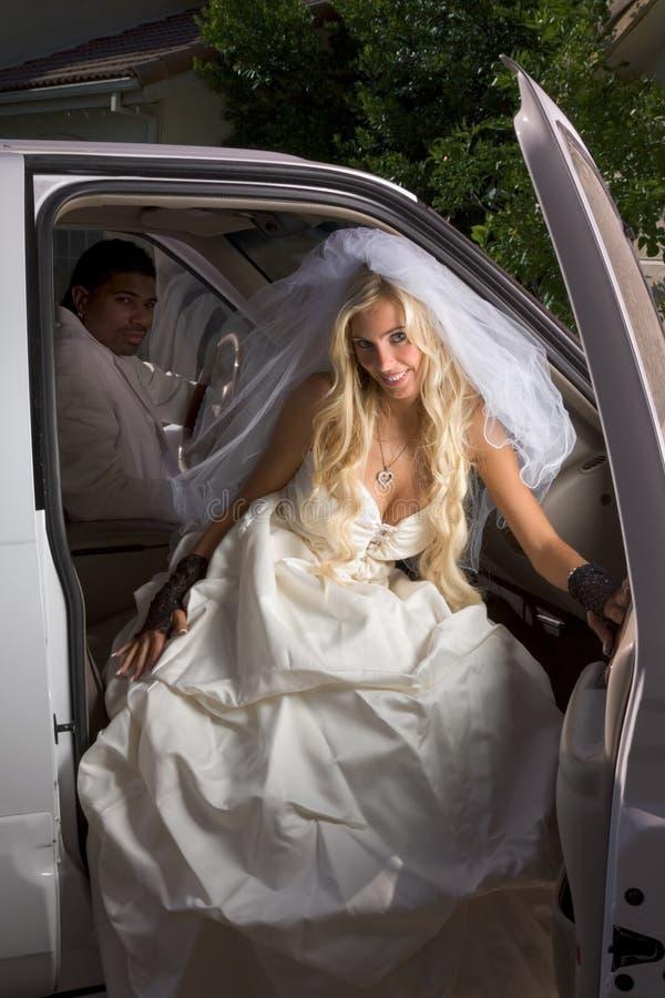 Novia joven en la alineada de boda que baja del coche imagen de archivo